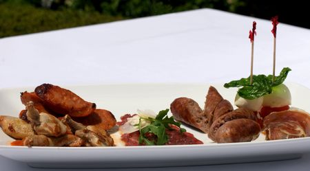 entree: An Entree selection plate offering Roasted Quail, Italian Sausages, Beef Carpaccio, Prosciutto, Tomato, and Bocconcini