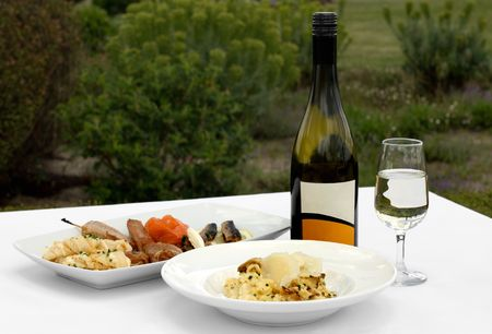 An Entree tasting plate, and a bowl of Mushroom Risotto, accompanied by a glass of Chardonnay photo