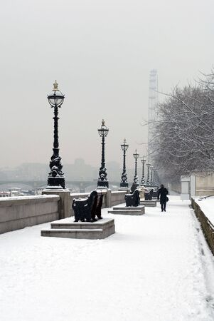 winter palace: A single pedestrian walking in the snow beside the River Thames, London, England Stock Photo