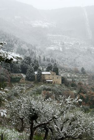 A solitary stone farmhouse in the Tuscan countryside, on a cold, snowy, Winters day. photo