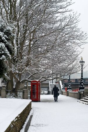 A red telephone box beside a walkway, on a cold Winter photo