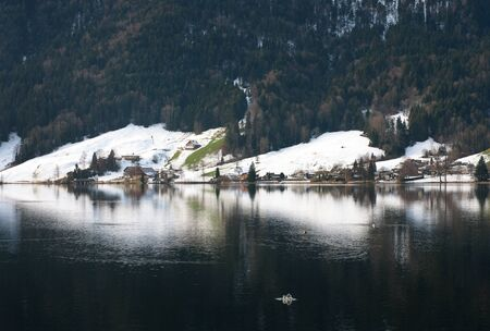 adjacent: A small alpine village adjacent to a lake, in Switzerland Stock Photo