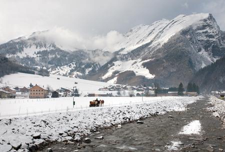 horse sleigh: A horse-drawn sleigh, on a path adjacent to a fast-flowing river, Austria