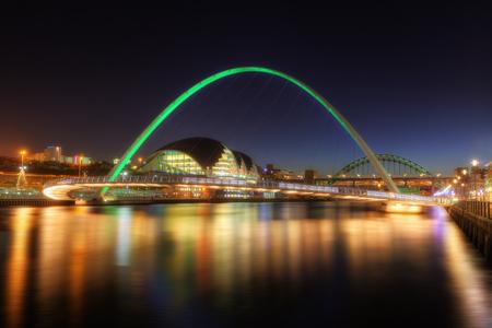 Night shot of the Gateshead Millennium Bridge, over the River Tyne, with the Tyne Bridge in the background.