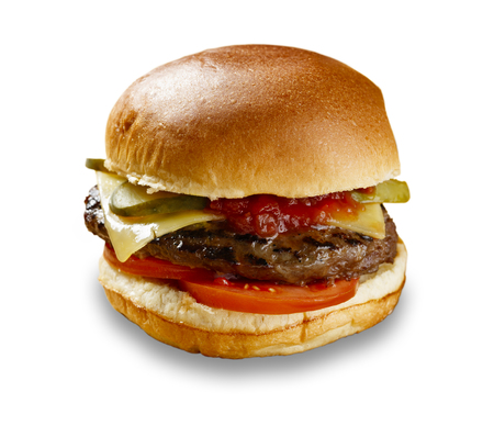 Delicious cheeseburger, pickles, tomate and relish, shot on white with a drop shadow
