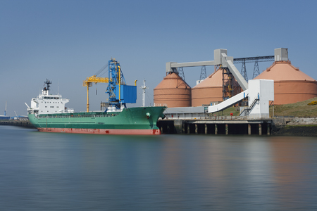 Unloading of a cargo ship in an industrial port, on a summers day with blue skies, and silos in background.