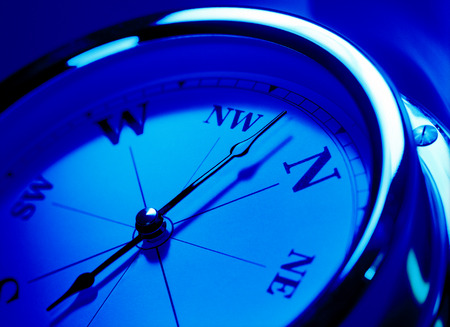close up of a compass with a blue tone effect, pointing north, north west.