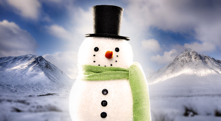 Snowman with top hat and scalf on snowy mountain background Фото со стока - 114915752