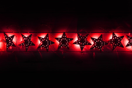 A string of red star christams lights on a dark wooden background, with room for copy or use as a banner.