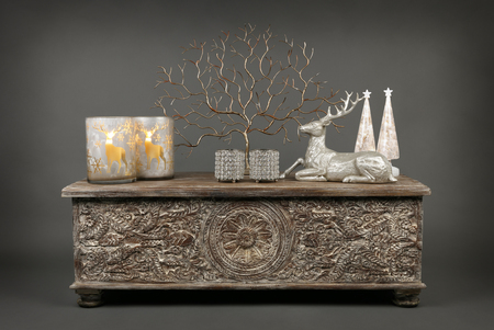 A selection of ornaments and decorations on an ottoman with a silver and gold Christmas feel, including tealights and candles, on a grey background Standard-Bild