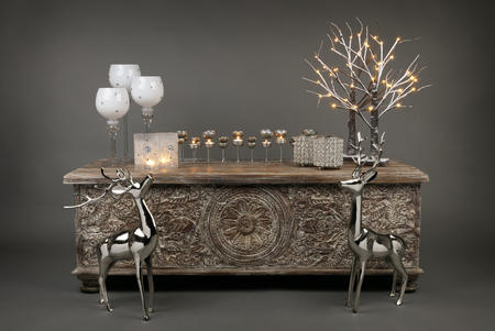 Ornaments and decorations on an ottoman with a silver and gold Christmas feel, including tealights and candles, on a grey background Standard-Bild
