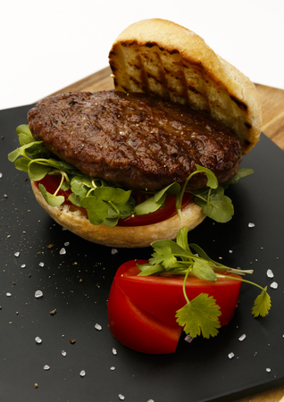 Succulent and juicy rare beef burger, with tomato and watercress garnish, in a bread bun, on a slate plate