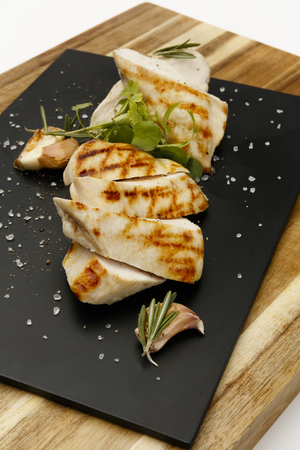 Seasoned succulent roasted chicken breast, with garlic and rosemary garnish, on a slate plate