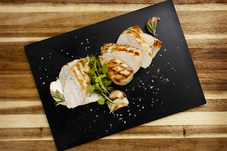 Plan view of seasoned succulent roasted chicken breast, with garlic and rosemary garnish, on a slate plate 版權商用圖片