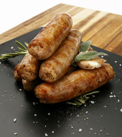 Seasoned tastey sausages with a garlic and herb garnish, on a slate plate