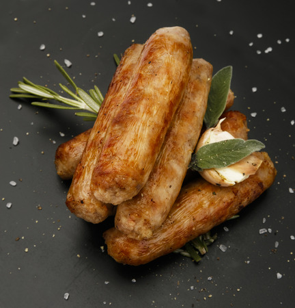 Grilled seasoned tastey sausages with a garlic and herb garnish, on a slate plate