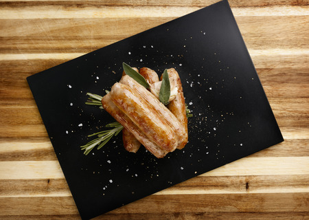 Plan view of  seasoned tastey sausages with a garlic and herb garnish, on a slate plate