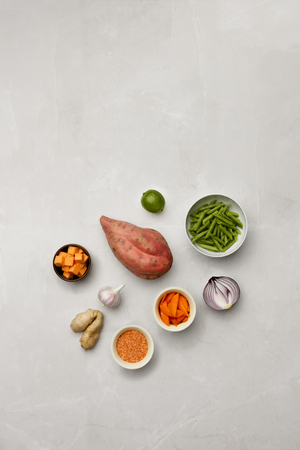 A selection of vegetable ingredients on a marble table top, with room for copy and text