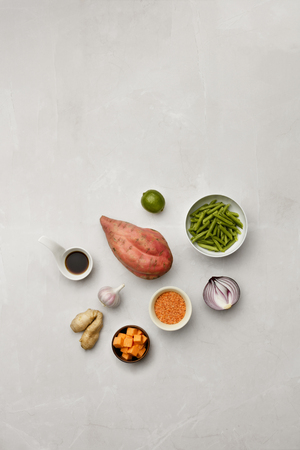 A selection of vegetable ingredients and soy sauce on a marble table top,  with room for copy and text