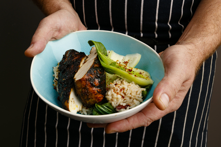 Close up of a chefs hands presenting a bowl of Jerk chicken with rice and vegetables and spices