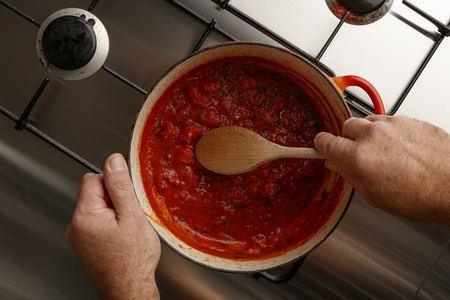 Plan view of a pot of traditional gormet tomato sauce and wooden spoon, on a stainless steal hob