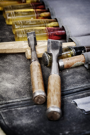 A grungy image of well used woodworking chisels side by side  in a chisel pouch