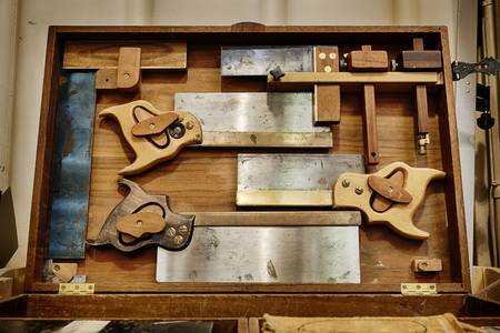 Traditional woodworking hand saws and carpentry tools in a cabinet 版權商用圖片