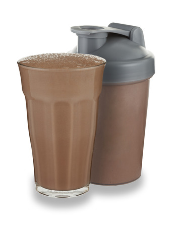 A glass of chocolate milkshake and shaker on a white background with a drop shadow