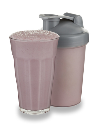 A glass of strawberry milkshake and shaker on a white background with a drop shadow