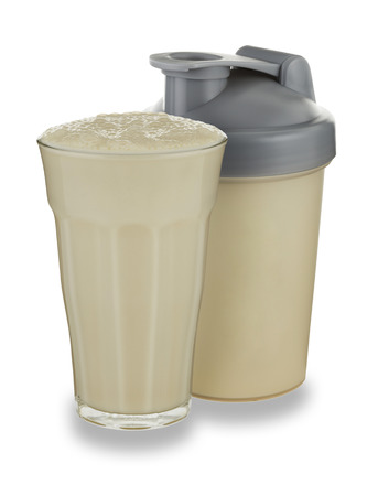 A glass of vanilla milkshake and shaker on a white background with a drop shadow 版權商用圖片