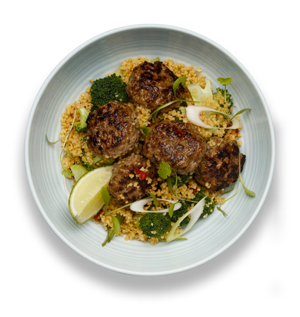 A bowl of succulent  Harissa Meat Balls on a bed of cuscus isolated on white with drop shadow 版權商用圖片