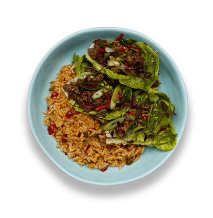 A bowl of succulent Spicy Beef Lettus Wraps on a bed of rice isolated on a white background with a drop shadow. 版權商用圖片