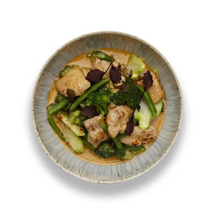 A bowl of succulent Thai Red Chicken Curry isolated on a white background with a drop shadow. 版權商用圖片
