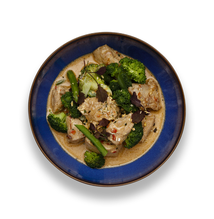 A blue bowl of succulent Thai Red Chicken Curry isolated on a white background with a drop shadow. 版權商用圖片