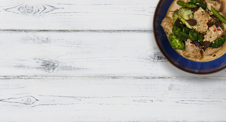 A blue bowl of succulent Thai Red Chicken Curry shot a white wooden background in a banner format with space for copy