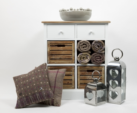 Chest of drawers, cushions, throws, ornaments and two candle holders on a white background