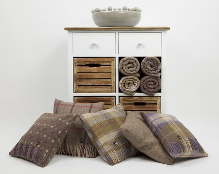 Wooden chest of drawers, cushions, throws, on a white background