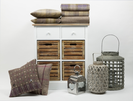 Chest of drawers, cushions, throws and ornaments on a white background