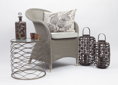 Wicker chair and cushions with a side table and two wicker candle holder on a white background