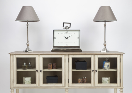 Glass fronted sideboard and ornaments with lamps and a large clock on a white background