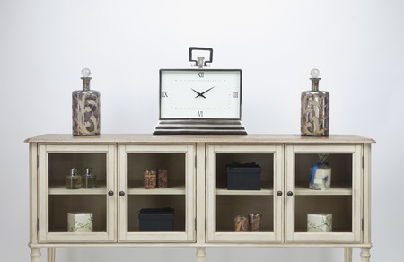 Glass fronted sideboard and ornaments and a large clock on a white background