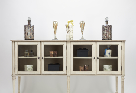 Glass fronted sideboard and ornaments on a white background