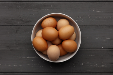 A bowl of fresh eggs on a distressed wooden background, shot from above