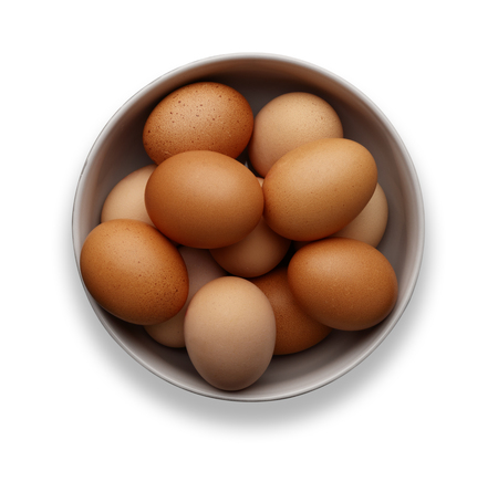 A bowl of fresh eggs on an isolated on a white background, shot from above 版權商用圖片