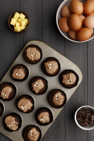 Fairy cakes in baking tray with  ingredients, on a distressed grey wooden background, shot from above 版權商用圖片