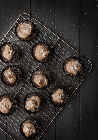 Fairy cakes on a cooling tray with sprinckled icing sugar on a distressed grey wooden background, shot from above