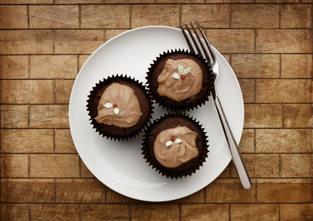 A white plate with  3 chocolate fairy cakes, and a fork on a wooden background, shot from above