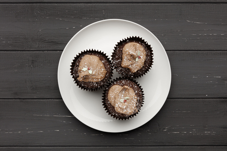 A white plate with  3 chocolate fairy cakes on a distressed wooden background, shot from above