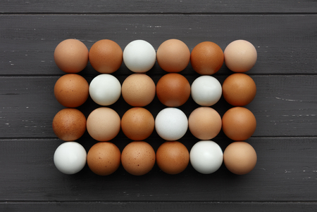 Rows of fresh eggs of various colours, shot from above on a distressed grey wooden background
