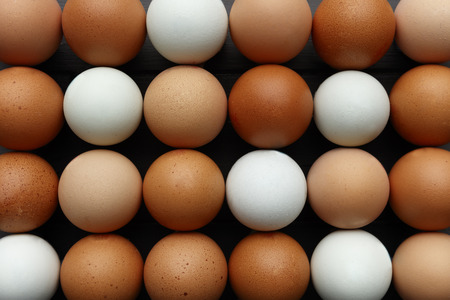 Rows of fresh eggs of various colours, shot from above filling the whole image